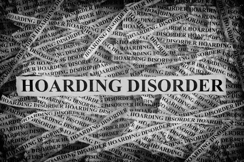 Canva Torn pieces of paper with the words Hoarding Disorder