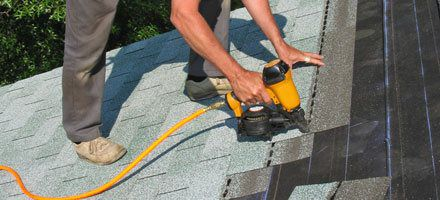 roofer using shingle gun to install new roof tiles