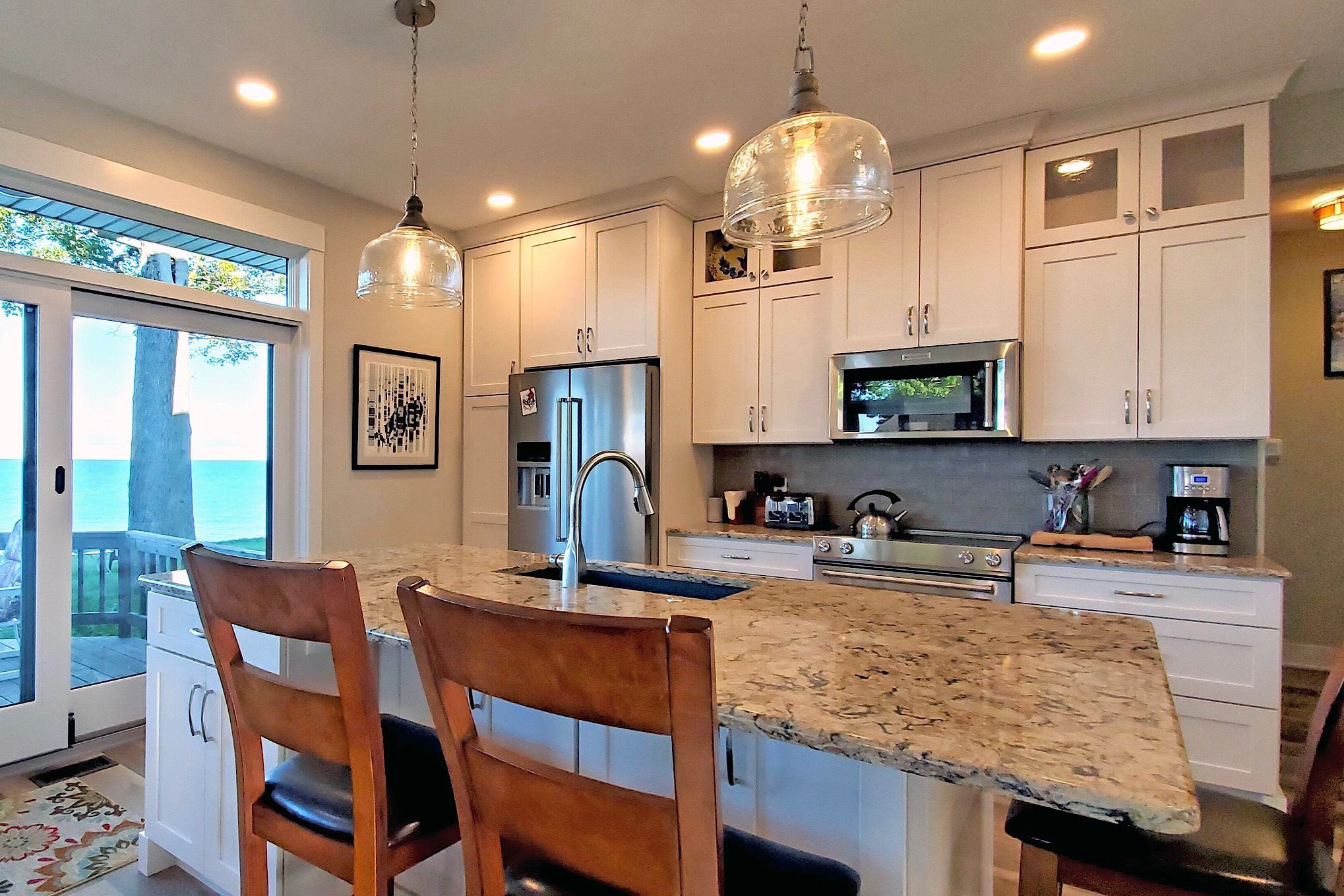 White shaker kitchen cabinets, hanging glass pendant lights, stainless steel appliances.