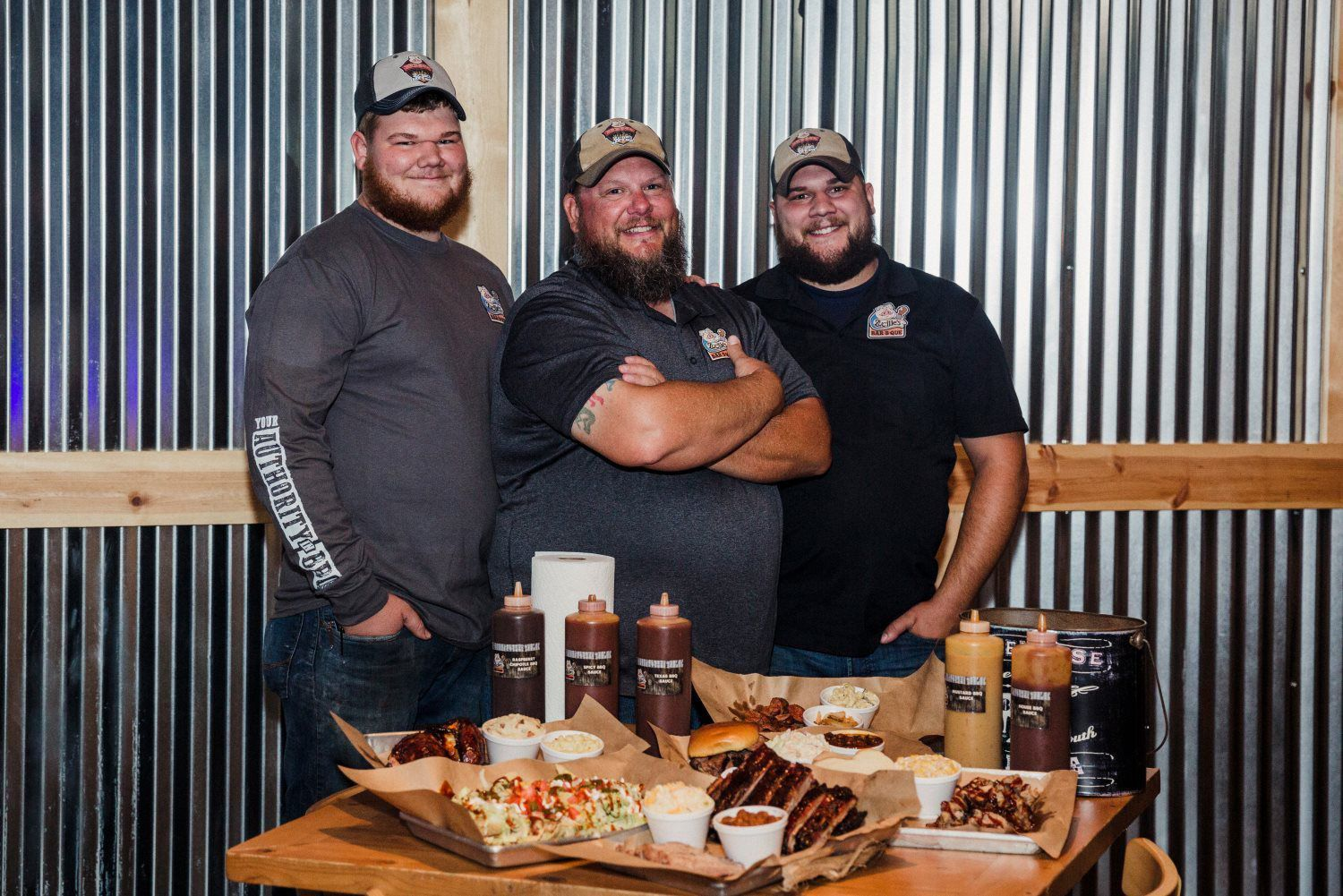 three large man with barbecue on the table